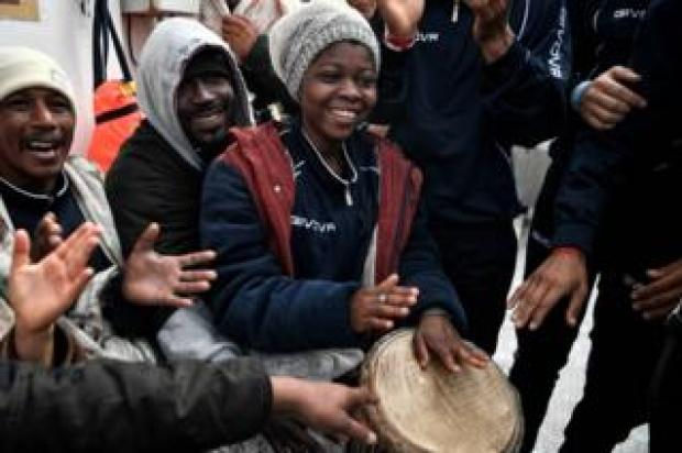 Migrants play music aboard MV Aquarius