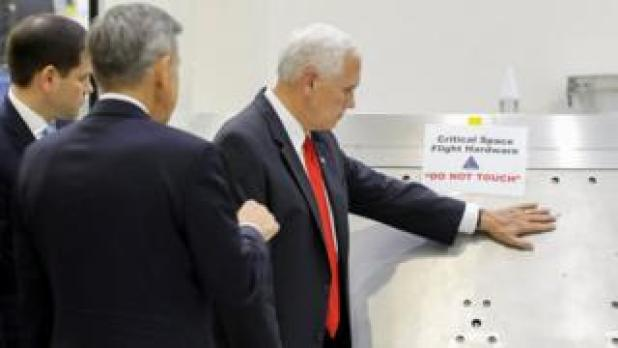 """US Vice-President Mike Pence touches a piece of hardware with a warning label """"Do Not Touch"""" at the Kennedy Space Center, 6 July 2017"""