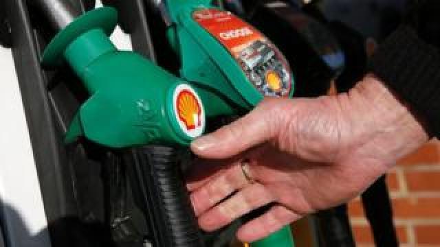 Man reaching for a fuel pump