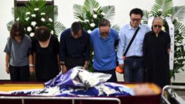 Liu Xia crying with other mourners beside her husband's coffin
