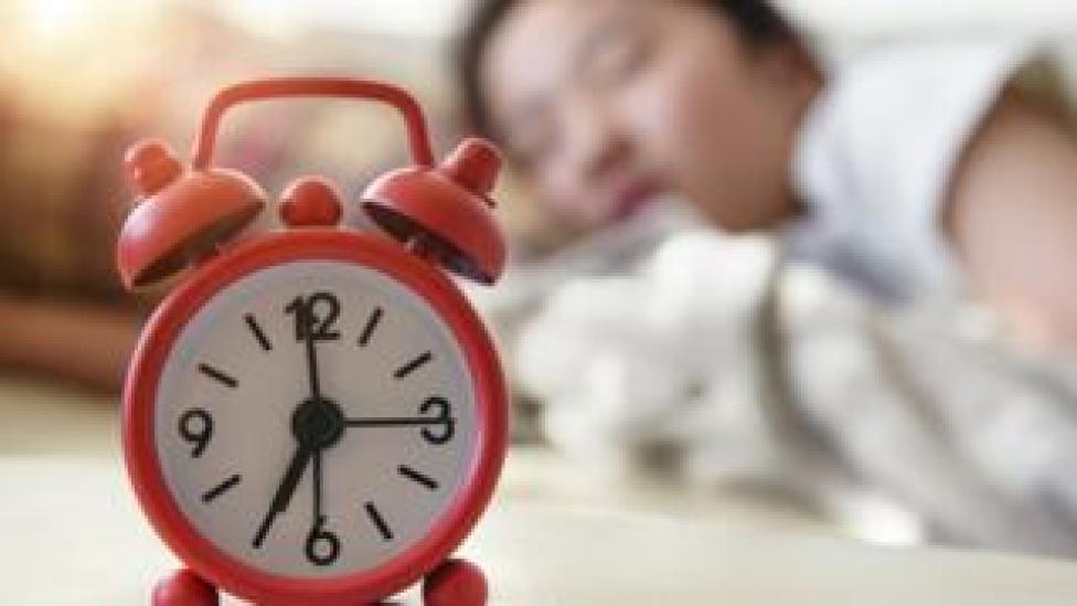 Une femme endormie avec un réveil