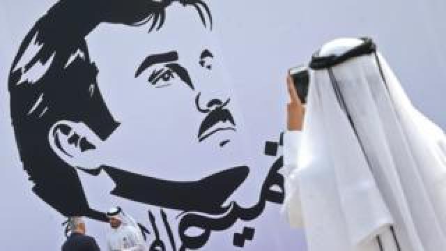 Qatari man takes a photo during the inaugural signing of a wall bearing a portrait of Qatar's Emir Sheikh Tamim bin Hamad Al Thani in Doha on 13 July 2017