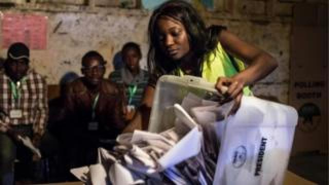 An Independent Electoral and Boundaries Commission (IEBC) official opens a ballot box at a polling station in Kiboro Primary School, in the Mathare slums of Nairobi on August 8, 2017,