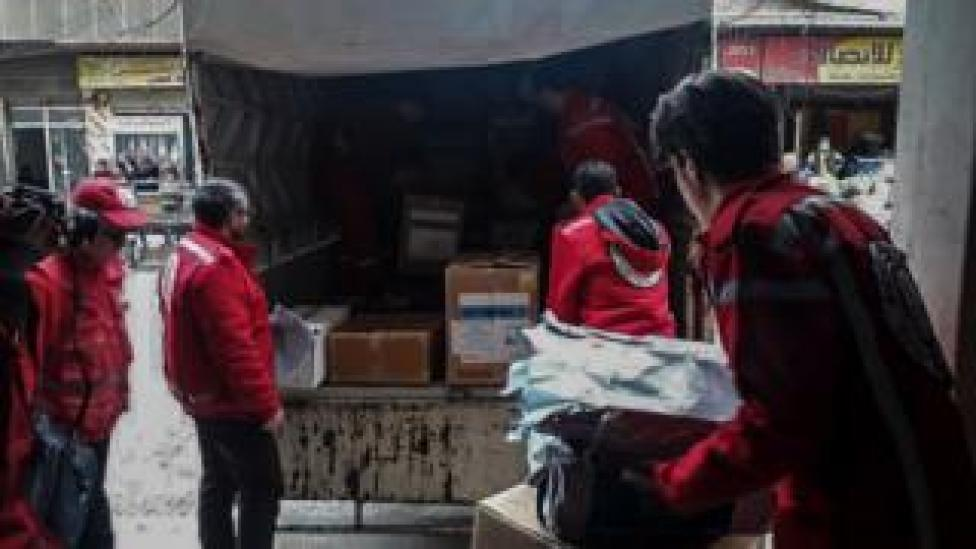 Six men working for the Syrian Arab Red Crescent unload boxes of supplies from the back of a truck