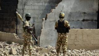 Soldiers looks at burnt house on 4 February 2016 during a visit to the village of Dalori village, some 12km from Borno state capital Maiduguri