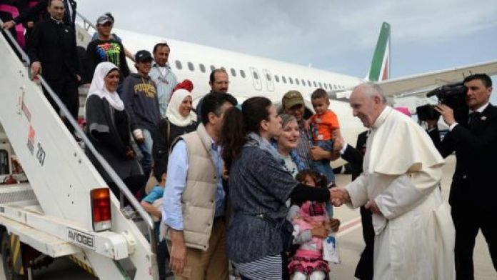 Pope Francis greets migrants stepping off a plane in Italy