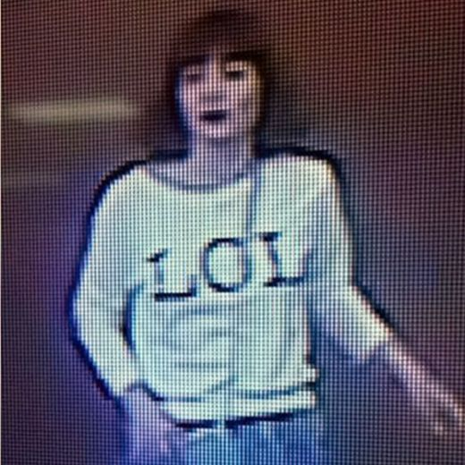Grainy image shows a woman with brown hair wearing a T-shirt with the letters