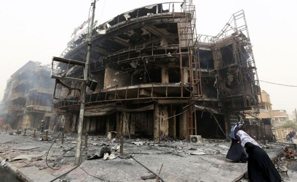 Iraqi women walk past a damaged building at the site of a suicide car bombing claimed by the Islamic State group on July 3, 2016 in Baghdad's central Karrada district