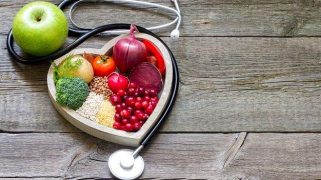 Grupo variado de comestibles con un estetoscopio en constituye de corazón.
