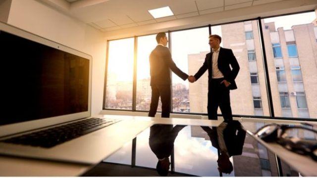 Dos personas dándose la mano en una oficina