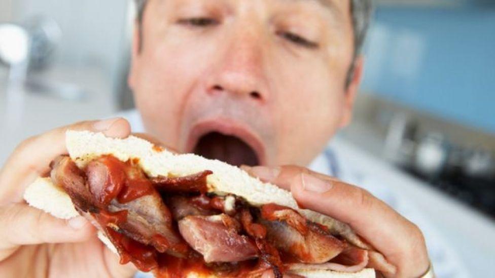 Homem comendo um sanduíche de bacon