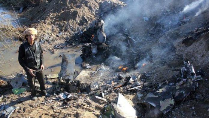 Combatiente de EI frente al avión de combate jordano derribado