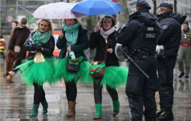 Carnival enthusiasts walk past members of the German police in Cologne