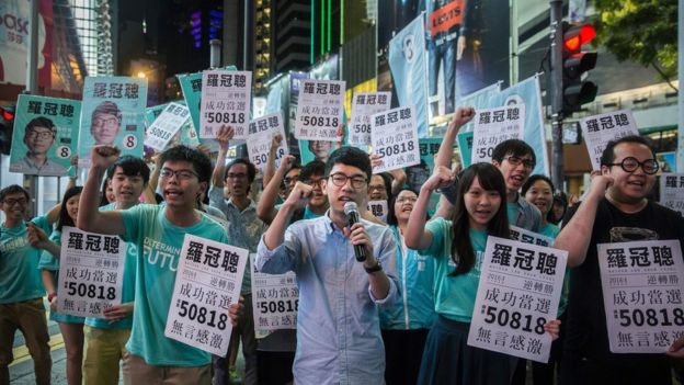 Nathan Law (C) speaks at a rally with Joshua Wong (centre L) and supporters in Causeway bay following Nathan Law's win in the Legislative Council election in Hong Kong on September 5, 2016