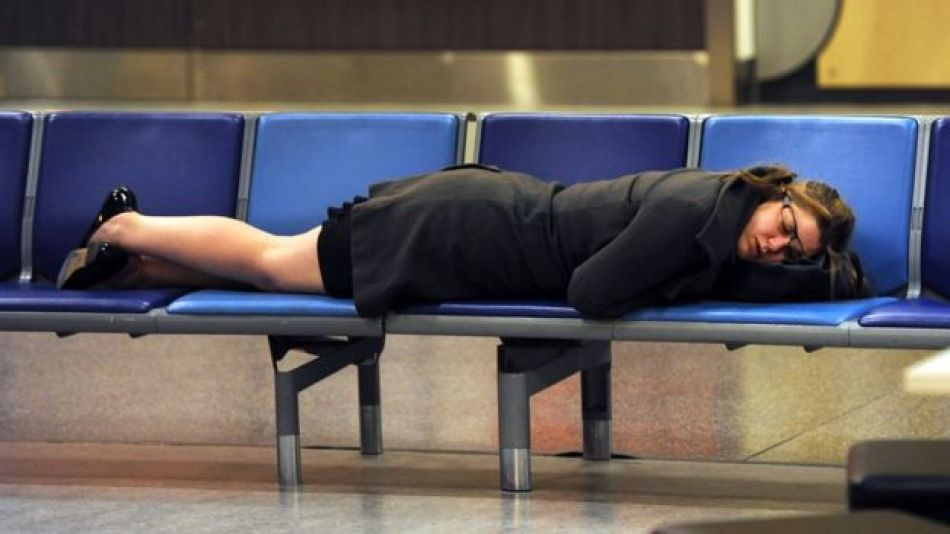 Mujer duerme en un aeropuerto.