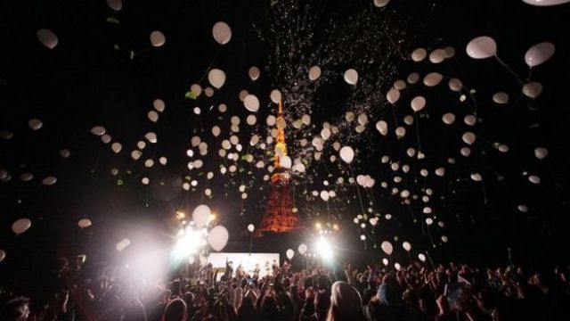 People release balloons to celebrate the New Year with Tokyo Tower in the background in Tokyo