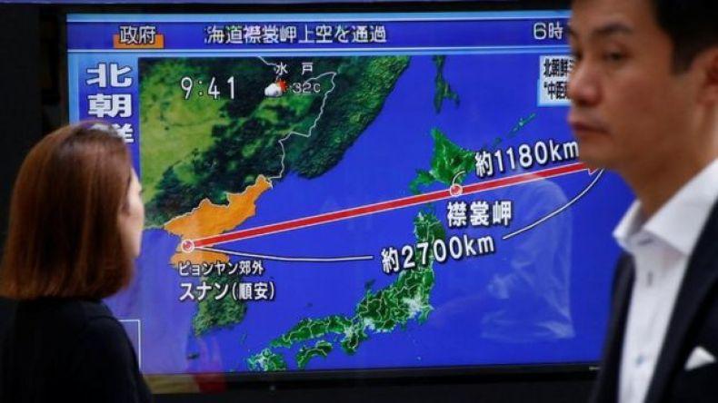 Espectadores viendo en la televisión el recorrido del misil