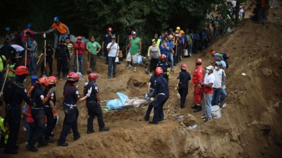 Firemen carry a body recovered from under the debris in the village of El Cambray II, in Santa Catarina Pinula municipality, some 15 km east of Guatemala City, on October 3, 2015 after a landslide late Thursday struck the village.