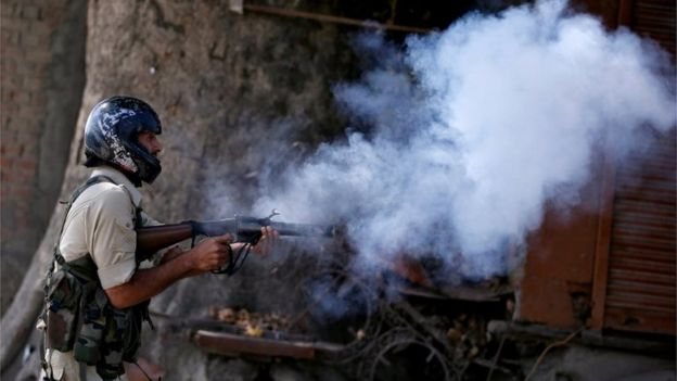 An Indian policeman fires a teargas shell towards demonstrators during a protest against the recent killings in Kashmir, in Srinagar on 23 September 2016.