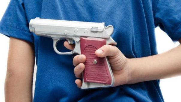 Un niño juega con una pistola de juguete