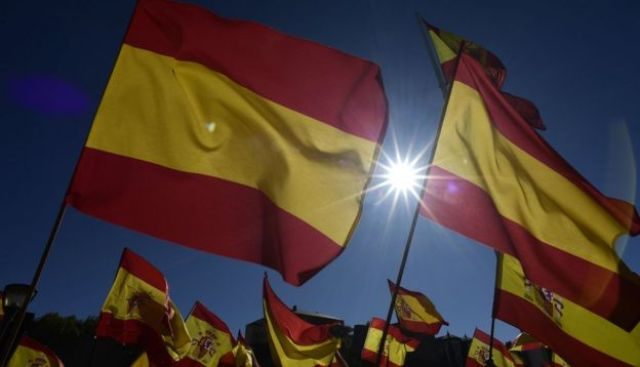 People wave Spanish flags during a demonstration calling for unity in Madrid on October 28, 2017,