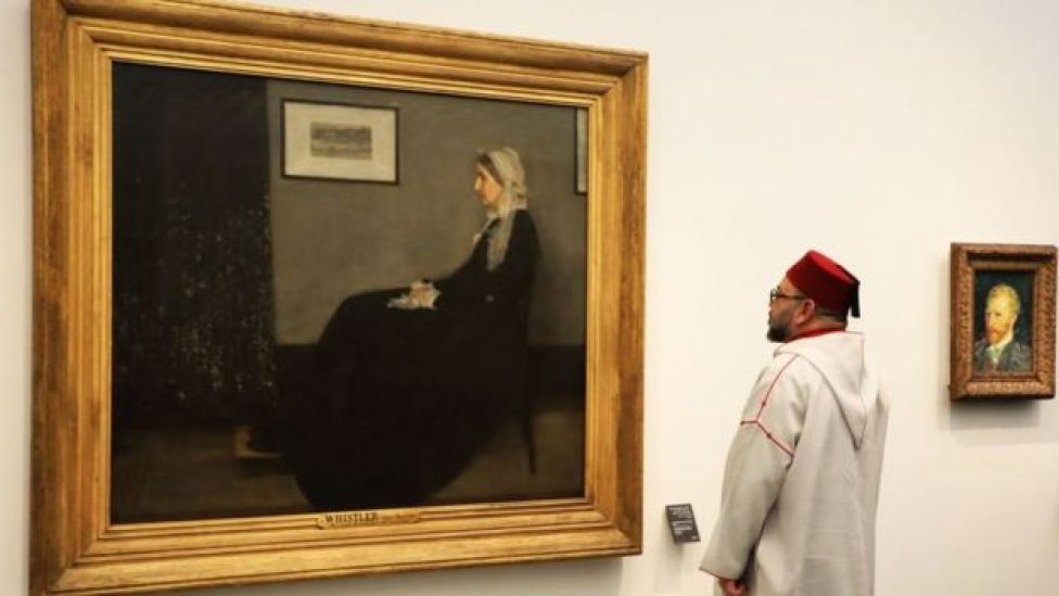 Moroccan King Mohammed VI looks at a painting titled 'Whistler's Mother' by James Abbott McNeill Whistler (1871) as he visits the Louvre Abu Dhabi Museum during its inauguration on November 8, 2017 on Saadiyat island in the Emirati capital
