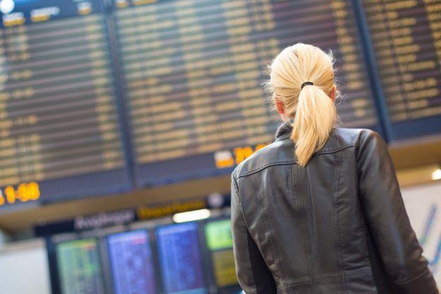 Mujer mirando pantalla en un aeropuerto
