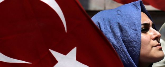 A woman holds a Turkish flag at a pro-government protest