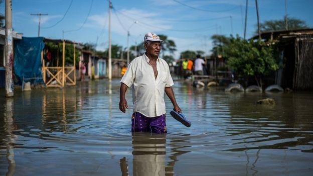 Hombre caminando por la calle con el agua pasando las rodillas.
