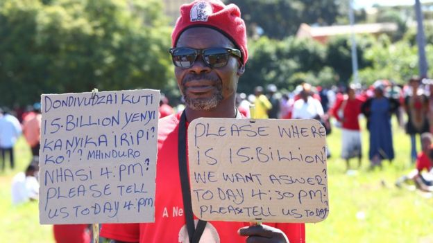 A supporter of the opposition party Movement for Democratic Change (MDC-T) holds placards during a protest against poverty and corruption, in Harare, Zimbabwe, 14 April 2016
