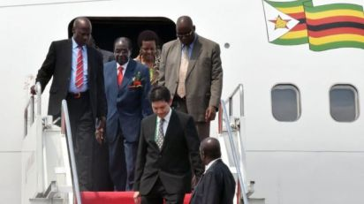 Zimbabwe's President Robert Mugabe (second on the left) disembarks from an aircraft after arriving at Halim airport in Jakarta (21 April 2015)