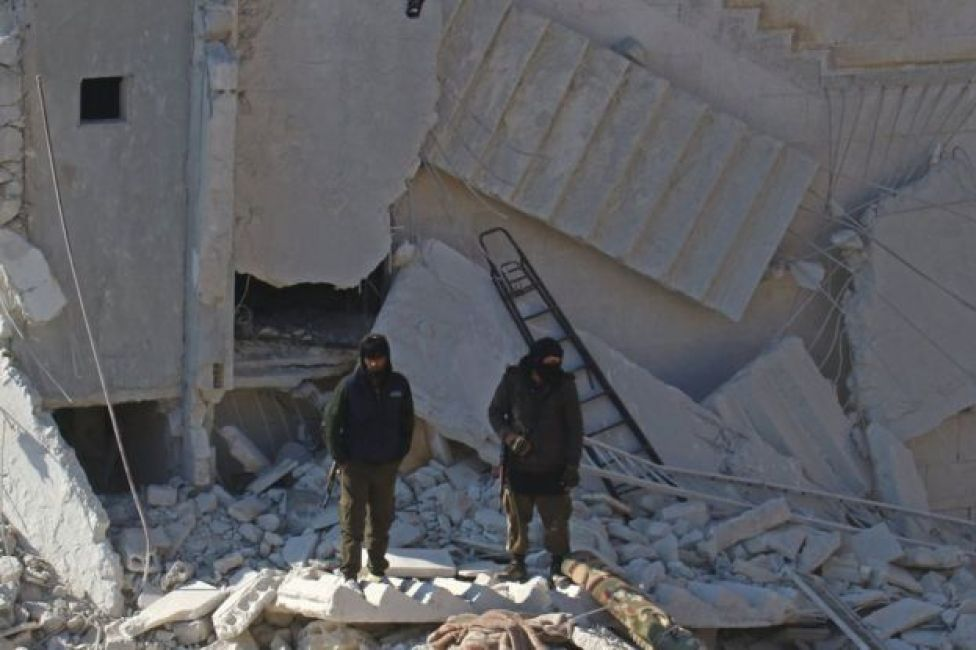 Rebel fighters stand next to building destroyed in air strike in rebel-held city of Idlib on 7 February 2017