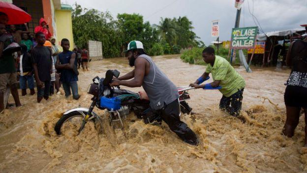 Men push a motorbike through a street flooded