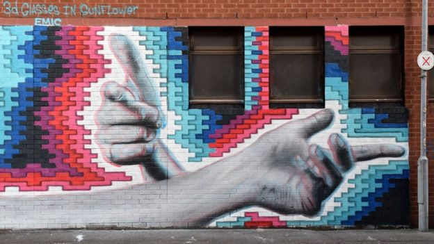A mural of two hands on a coloured background