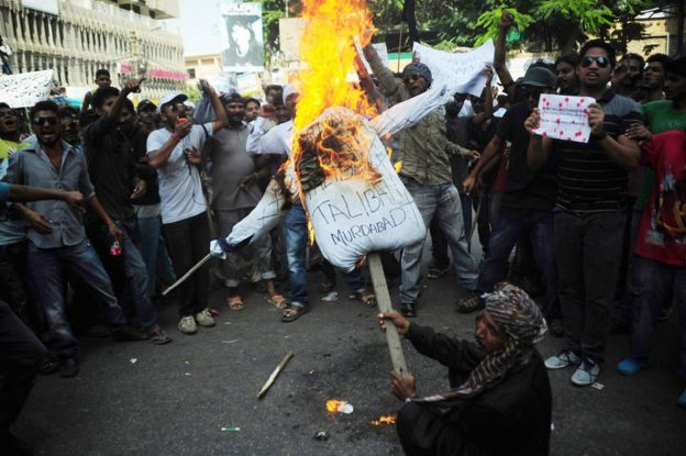 Pakistani Christian burn an effigy of the Taliban during a protest in Karachi on 23 September 2013, in reaction to bomb attacks at a church in Peshawar.