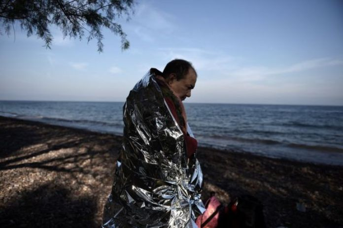 A man in a foil blanket for keeping warm, on the beach, December 8, 2015