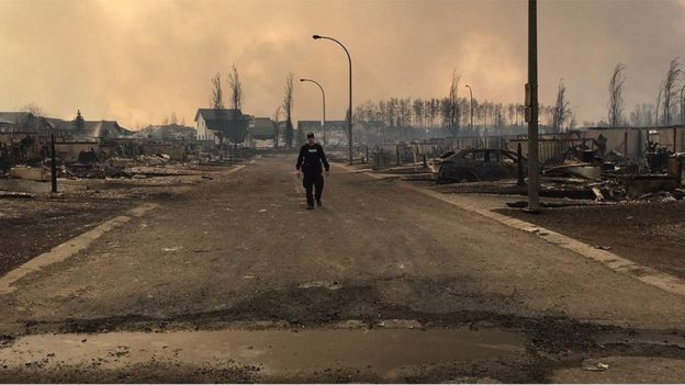A Mountie surveys the damage on a street in Fort McMurray, 5 May 2016