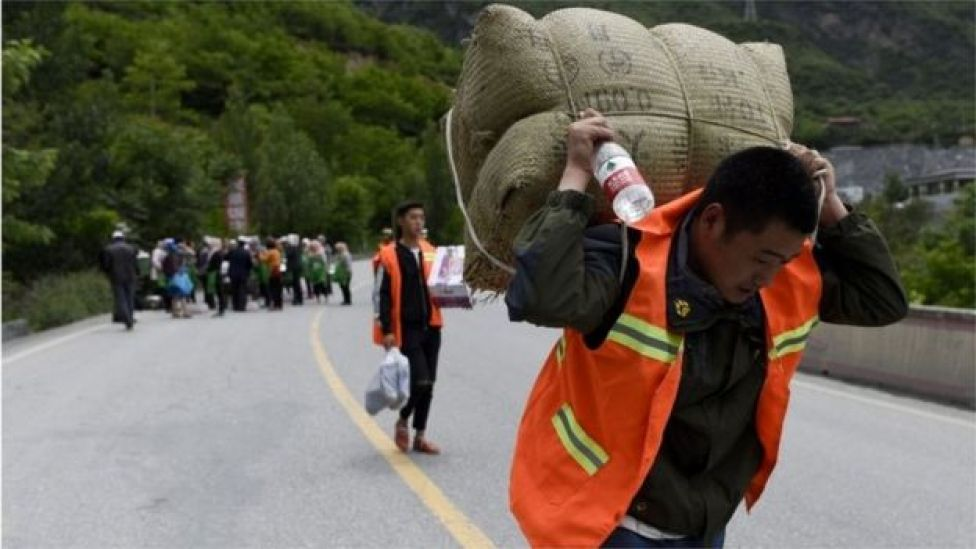 A man carries supplies as he heads to a landslide area in the village of Xinmo in Maoxian county, China's Sichuan province 25 June 2017