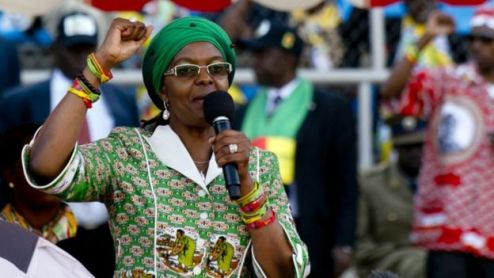 Grace Mugabe is pictured holding her hand in the air addressing a crowd