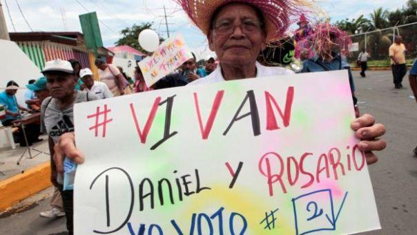 Un hombre con un letrero de apoyo a Daniel Ortega y Rosario Murillo.