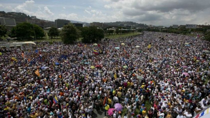 A mass of people take a highway during a protest against President Nicolas Maduro in Caracas, Venezuela, Wednesday, Oct. 26, 2016.
