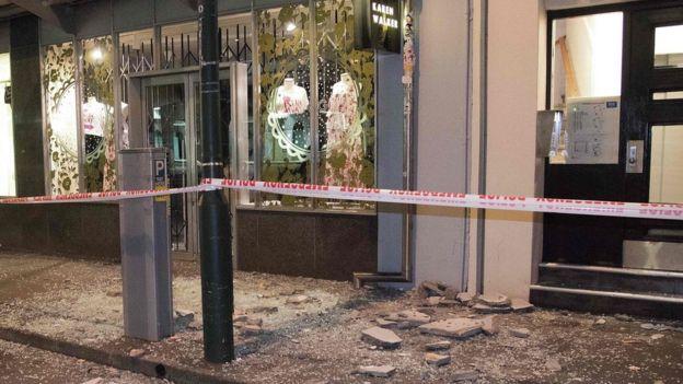 Debris from buildings are seen on a sidewalk past a cordon line in Wellington