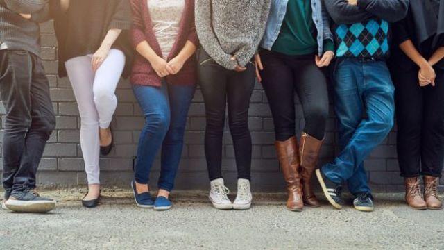 Jóvenes recostados en una pared