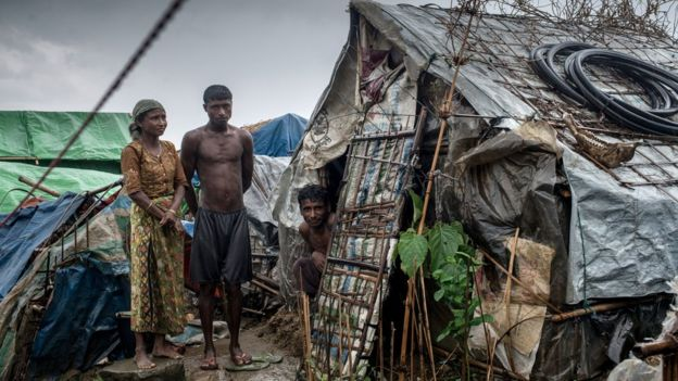 A family stands outside their hut in one of the unregistered IDP camps, May 24, 2015 in Sittwe, Myanmar. Since 2012, the minority group of the Rohingya people are forced to live in IDP camps, in Rakhine State in western Burma