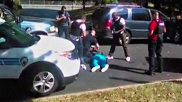 Agentes rodean a Scott, quien yace en el suelo