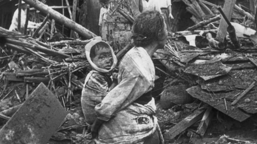 Mulher carrega bebê após explosões em Pyongyang