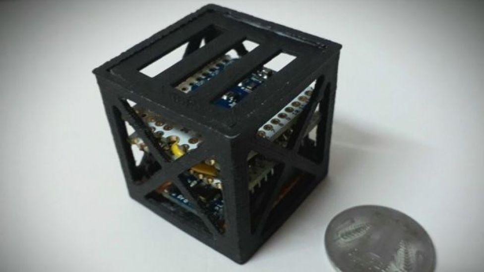 A small satellite cube next to a coin