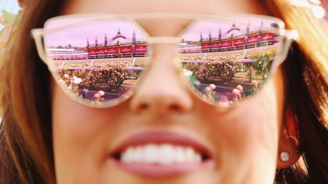 The winning post reflected in a race-goer's sunglasses