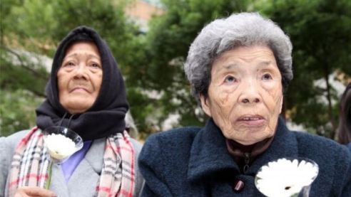 A picture made available 26 December 2015 shows former Philippine comfort woman, Estelita B. Dy (L), and former Taiwan comfort woman, Cheng Chen-tao (R), commemorating deceased comfort women outside Japan