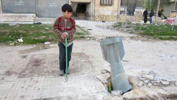 Criança observa bomba de fragmentação na Síria, em 2013